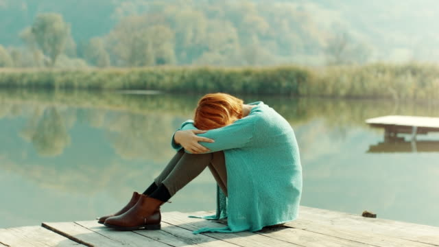vídeos de stock e filmes b-roll de sad woman sitting on pier with her head between legs - só mulheres jovens