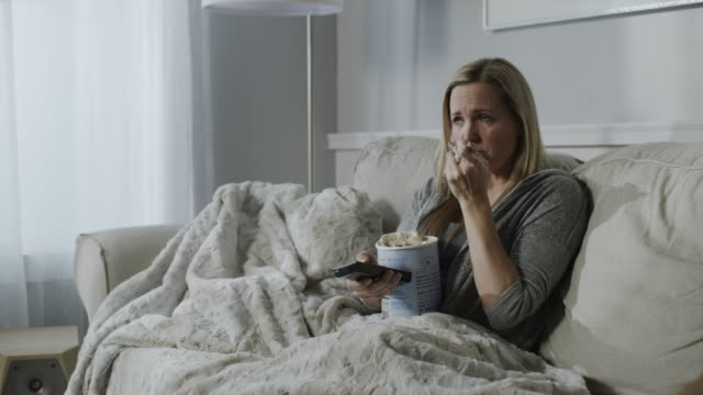 sad woman sitting on sofa eating ice cream and watching television / cedar hills, utah, united states - facial expression stock videos & royalty-free footage