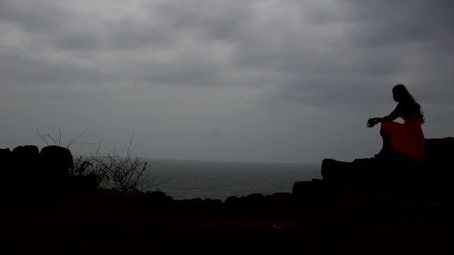 stockvideo's en b-roll-footage met treurige vrouw zittend op de muur in de buurt van de zee - alleen één tienermeisje