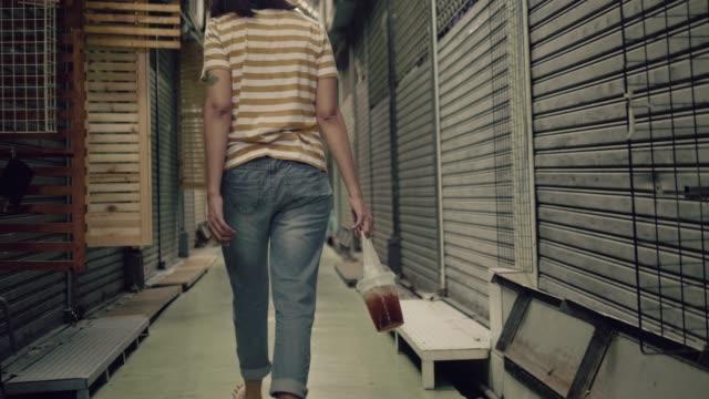 stockvideo's en b-roll-footage met triest jonge aziatische vrouw lopen alleen in nauwe winkel - teleurstelling
