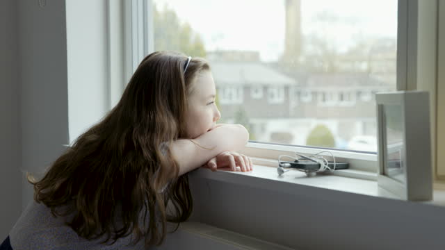sad young girl looking out of window. she leaves her smartphone - children only stock videos & royalty-free footage
