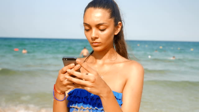 vidéos et rushes de triste jeune fille sur la plage des problèmes à l'aide de téléphone intelligent à la plage - blog
