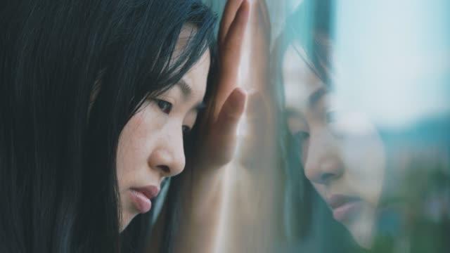 vídeos de stock, filmes e b-roll de triste jovem mulher perto da janela - desesperança