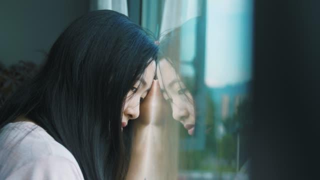 窓のそばの悲しい若い女性 - 景色を眺める点の映像素材/bロール