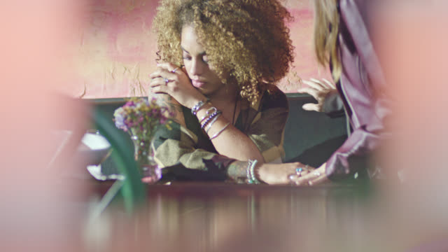 sad young woman is comforted by her partner at restaurant table. - grief stock videos & royalty-free footage