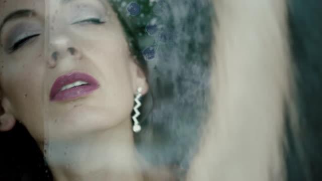 traurige junge frau blick durch fenster mit regentropfen - verführerische frau stock-videos und b-roll-filmmaterial