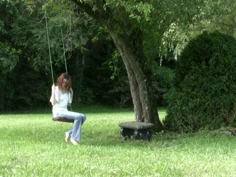 sad young woman sits on a rope swing ntsc - fruit tree stock videos & royalty-free footage