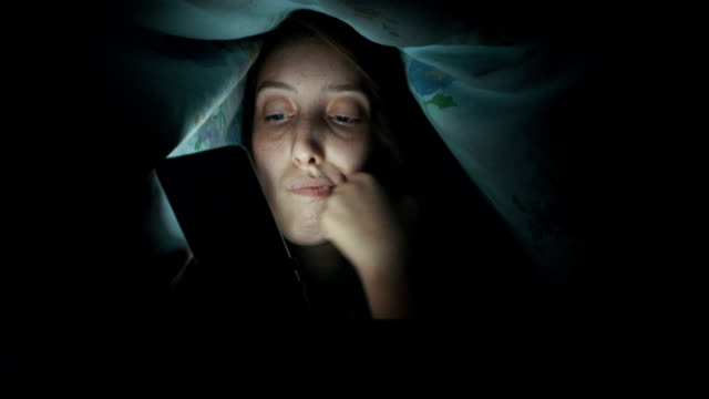 Sad young woman using phone under blanket