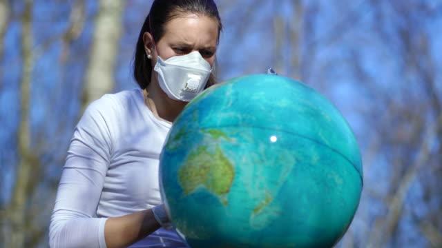 vídeos de stock, filmes e b-roll de mulher triste jovem com máscara de rosto n95 olhando para o globo ao ar livre - batendo com a cabeça na parede
