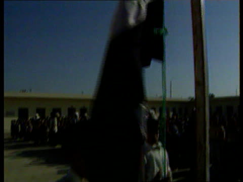 baghdad gvs men in cafe sitting watching iraqi president saddam hussein's television address ms young boy hoisting iraqi flag on flagpole as... - saddam hussein stock videos & royalty-free footage