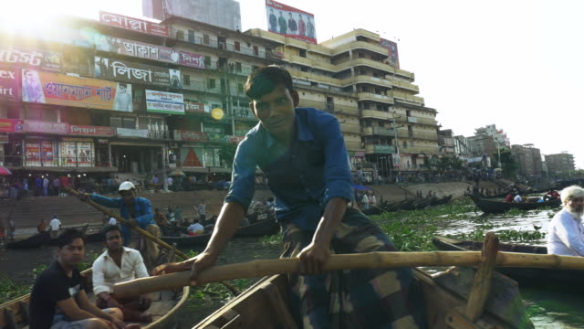 Sadarghat Launch Terminal in Dhaka Bangladesh is a bustling passenger transport hub where tiny wooden boat taxis paddle alongside huge steel ferries