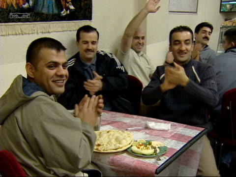 saddam hussein capture: evening news; 18.00: john ray england: manchester: int iraqi kurds in cafe celebrating the capture of saddam hussein cms... - itv evening news stock-videos und b-roll-filmmaterial