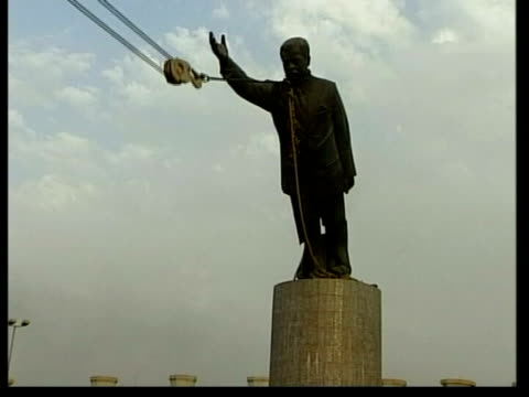 saddam hussein capture: evening news; lib day statue of saddam being toppled tilt down cms iraqi people standing on the face of the statue - statue stock videos & royalty-free footage