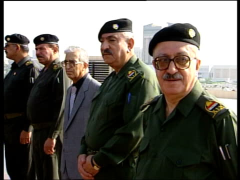 Saddam Hussein message of defiance ITN Baghdad Iraqi politicians saluting as standing in line during ceremony PAN SIDE MS Iraqi politicians standing...