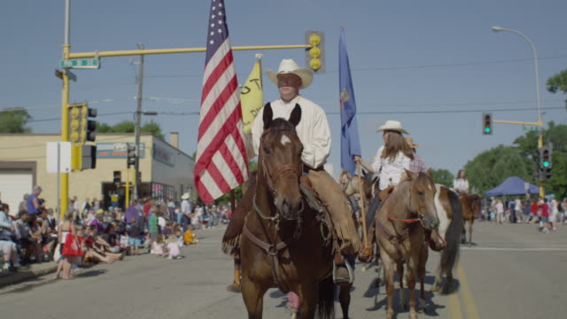 Saddle club cowboys ride their horses past camera in a small town parade.