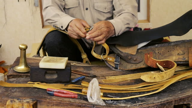 saddler. saddle manufacture. leather goods craftsman at work in his workshop. - gambe incrociate video stock e b–roll