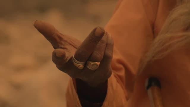 C/U sadhu praying in the Ganges river, hand