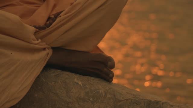C/U TILT UP sadhu praying in the Ganges river