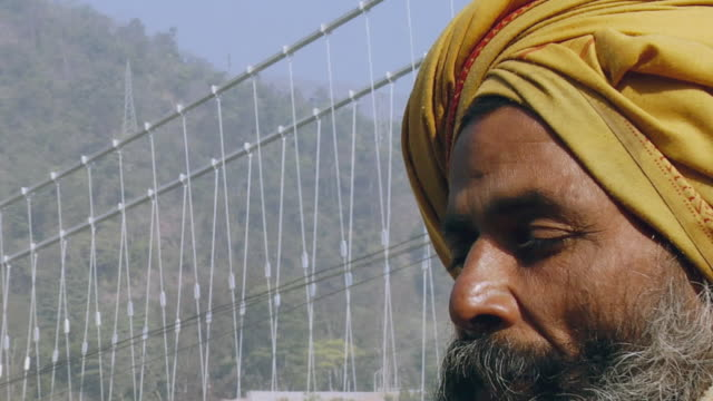 vídeos de stock, filmes e b-roll de cu zo sadhu praying, laxman jhula bridge in background / rishikesh, uttarakhand, india - rishikesh