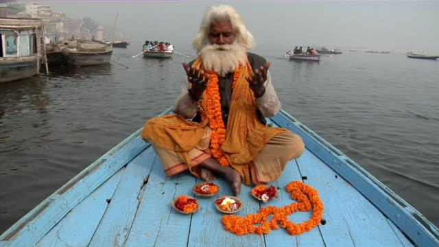 WS, Sadhu praying on boat in Ganges river, Varanasi, Uttar Pradesh, India
