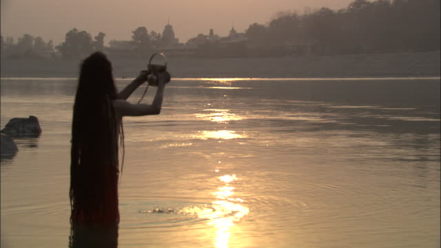 Sadhu raises pitcher of water from River Ganges, Rishikesh Available in HD.