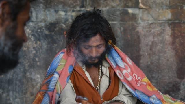 sadhu smoking pipe with marijuana. - グジャラート州点の映像素材/bロール