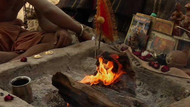 ms zo sadhu worshiping near river  / pushkar, rajasthan, india - korslagda ben bildbanksvideor och videomaterial från bakom kulisserna