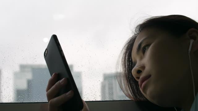 悲しみの女性が雨の日に音楽を聴く - 対立点の映像素材/bロール