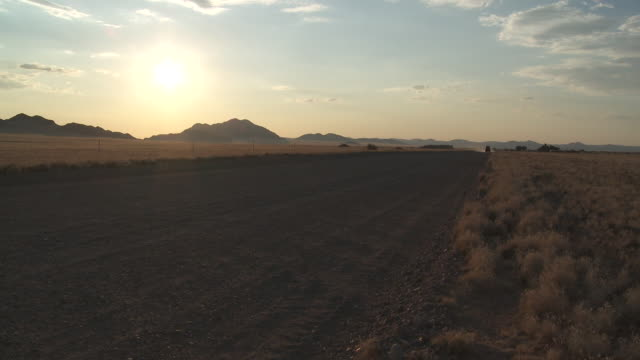 a safari jeep drives along a road in the namib desert at golden hour. - golden hour stock videos & royalty-free footage