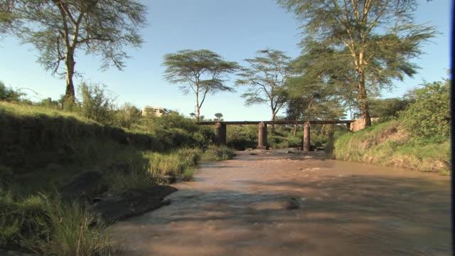 MS, TU, Safari vehicle crossing bridge over muddy river, Masai Mara, Kenya