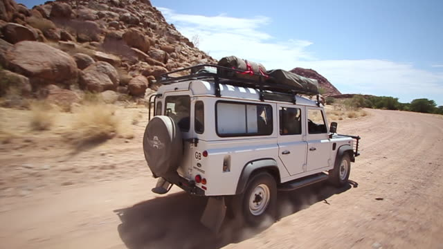 ms pov safari vehicle driving through namibian desert / windhoek, namibia - 四輪駆動車点の映像素材/bロール