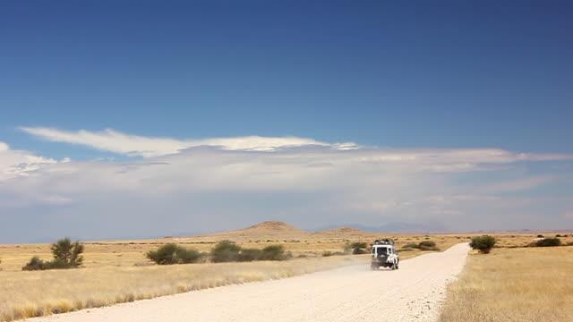 ws safari vehicle driving through namibian desert / windhoek, namibia - namibian desert stock videos and b-roll footage