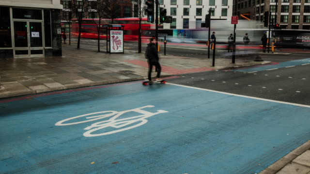 vídeos de stock e filmes b-roll de a safe blue zone for cyclists using london cycle superhighway on a busy junction during the early morning rush hour - road junction
