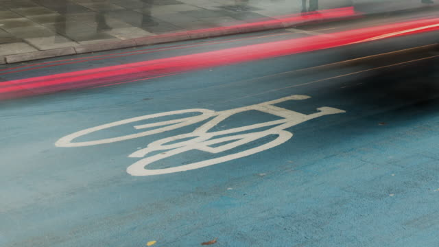 vídeos de stock e filmes b-roll de a safe blue zone for cyclists using london cycle superhighway on a busy junction during the early morning rush hour - material