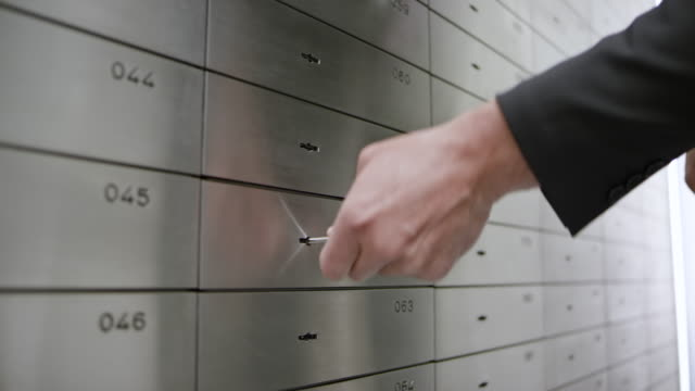 ds safe deposit clerk granting access to the safe deposit box to a female customer opening it with her key - alloy stock videos & royalty-free footage