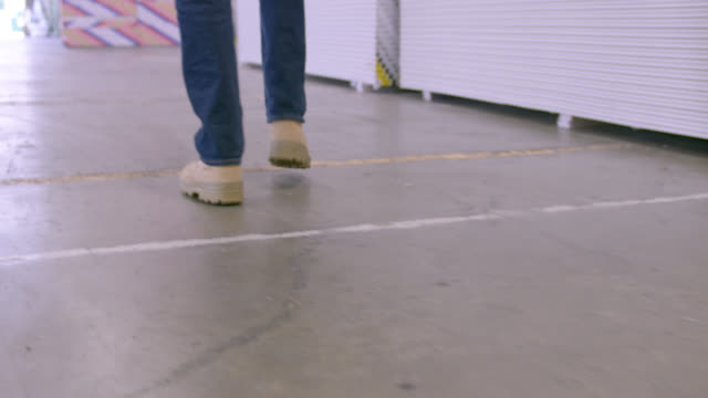 LA CU SLOMO safety boots of worker walking through warehouse