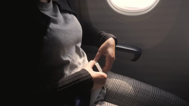 safety concept asian woman is fastening seat belt on airplane  ready to take off - vehicle seat stock videos & royalty-free footage