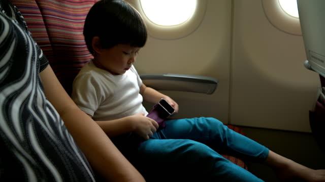 sicherheit konzept junge schnallen am sitz im flugzeug während des fluges reisen. - sicherheitsgurt sicherheitsausrüstung stock-videos und b-roll-filmmaterial