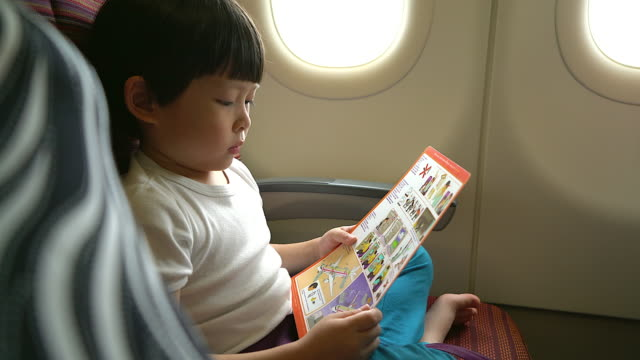 Safety concept young boy reading safety instruction on airplane during flight travelling.