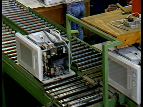 safety doubts; itn lib luton microwaves along conveyor in factory; - 電子レンジ点の映像素材/bロール
