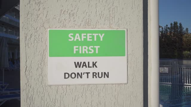 """""""safety first. walk, don't run"""" information sign on the column near swimming pool - information sign stock videos & royalty-free footage"""