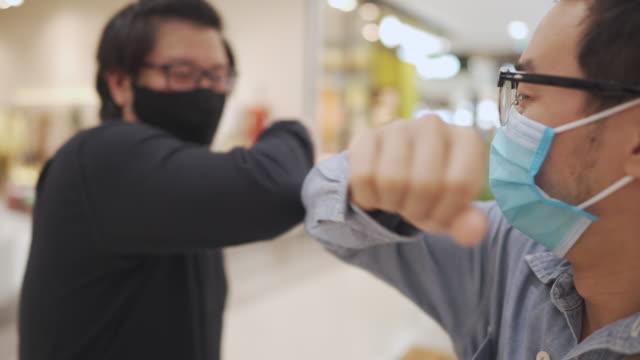 vídeos y material grabado en eventos de stock de saludo de seguridad de dos amigos asiáticos en los grandes almacenes en la situación del virus covid-19 corona - codo