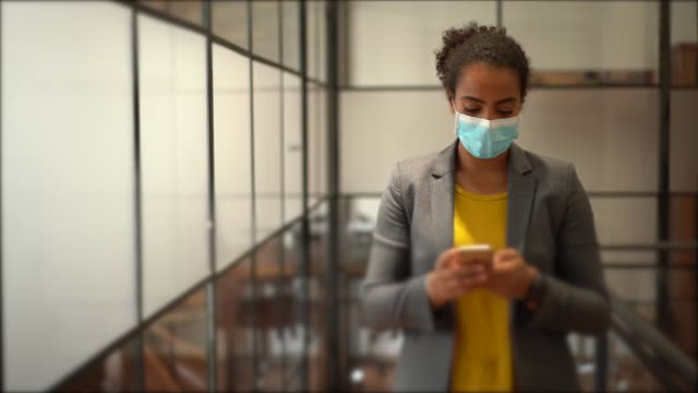 vídeos de stock e filmes b-roll de safety in the office during covid-19 pandemic, businesspeople with face masks - miscigenado