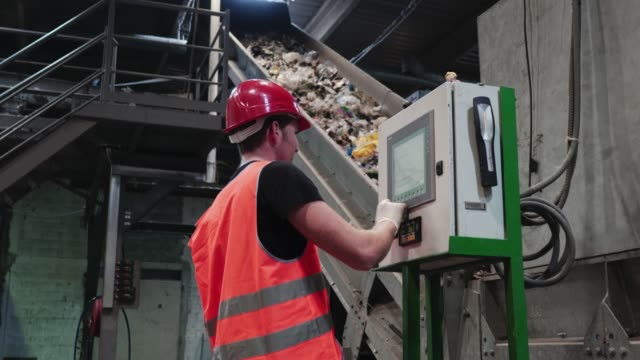 safety inspector having a look at a machine that controls the conveyor belt - attrezzatura industriale video stock e b–roll