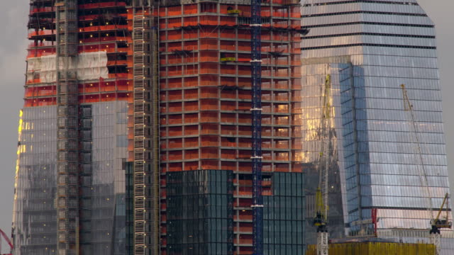 safety netting around skyscraper construction sites blows in the wind. glass exteriors reflect evening light. - gru video stock e b–roll