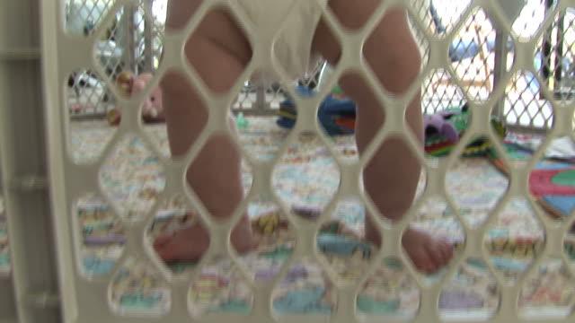 (hd1080i) sicherheit, schutz: baby steht im spiel stift, schwenk nach oben - ein männliches baby allein stock-videos und b-roll-filmmaterial