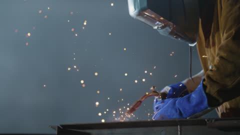 vídeos y material grabado en eventos de stock de slo mo cu safety-conscious welder puts on face mask for protection against sparks - típico de la clase trabajadora