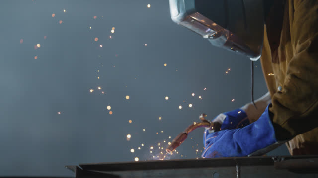 slo mo cu safety-conscious welder puts on face mask for protection against sparks - stereotypically working class stock videos & royalty-free footage