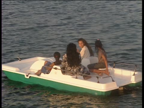 Safia Gaddafi and daughter Aisha in a pedal boat as other guests relax on shore at Muammar Gaddafi's seaside compound in Tripoli