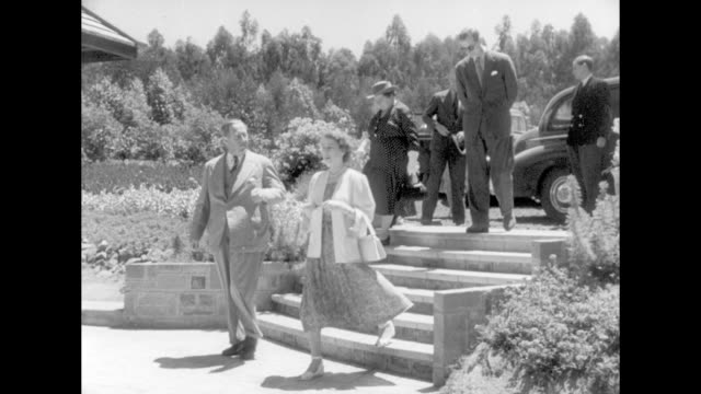 ws sagana state lodge and lawn / open door to the building / pan princess elizabeth is escorted down exterior stairs by the governor of kenya sir... - garden path stock videos and b-roll footage